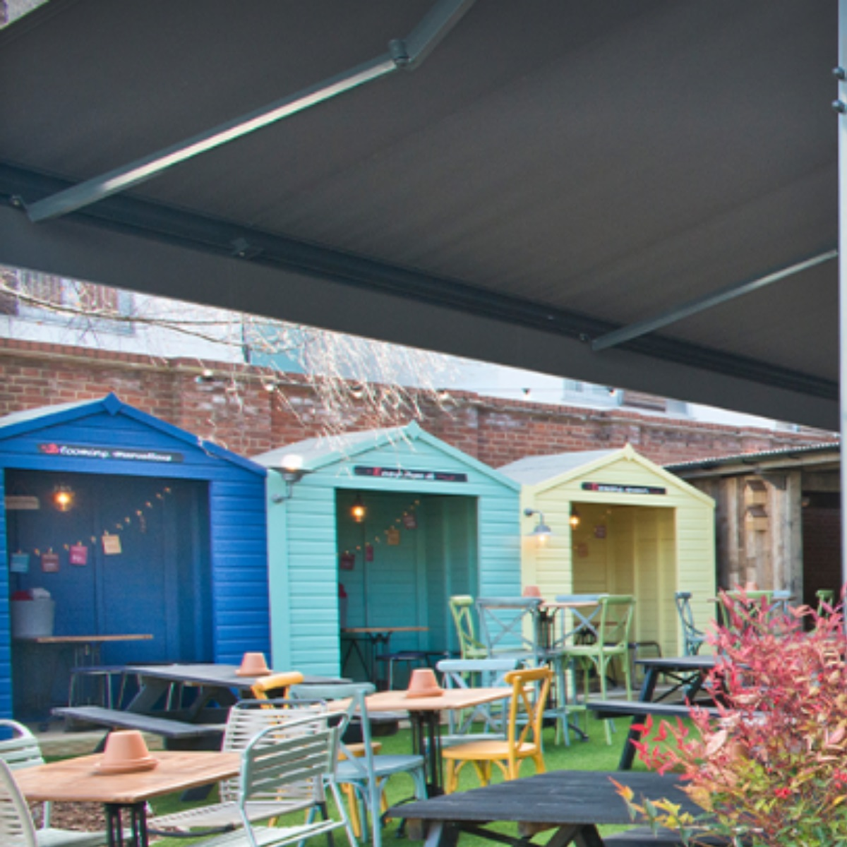 Brightly coloured wooden cabins that look like beach huts in a pub garden for people to sit in undercover