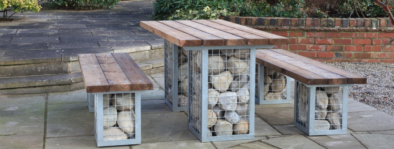 A garden furniture set with a rectangular table and 2 matching benches. They have steel cages filled with large cobble stones as the legs and wooden table and bench tops located on a patio