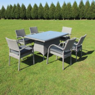 A large rectangular outdoor table and 6 chairs in grey rattan with a glass table top located on a lawn