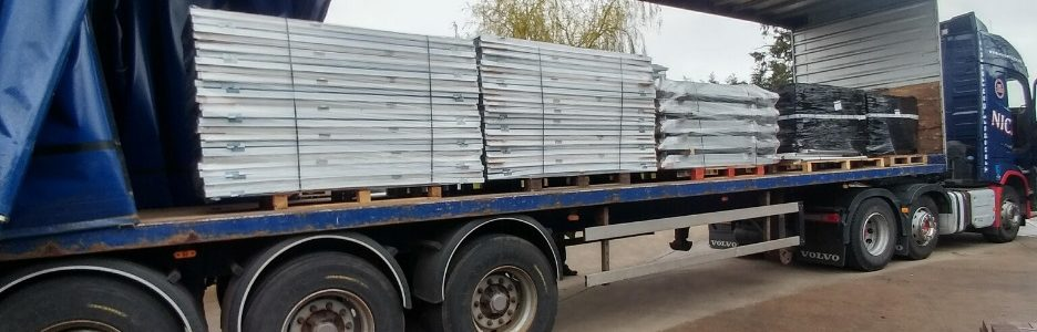 3 stacks of white plastic hospital doors loaded onto a lorry ready for delivery