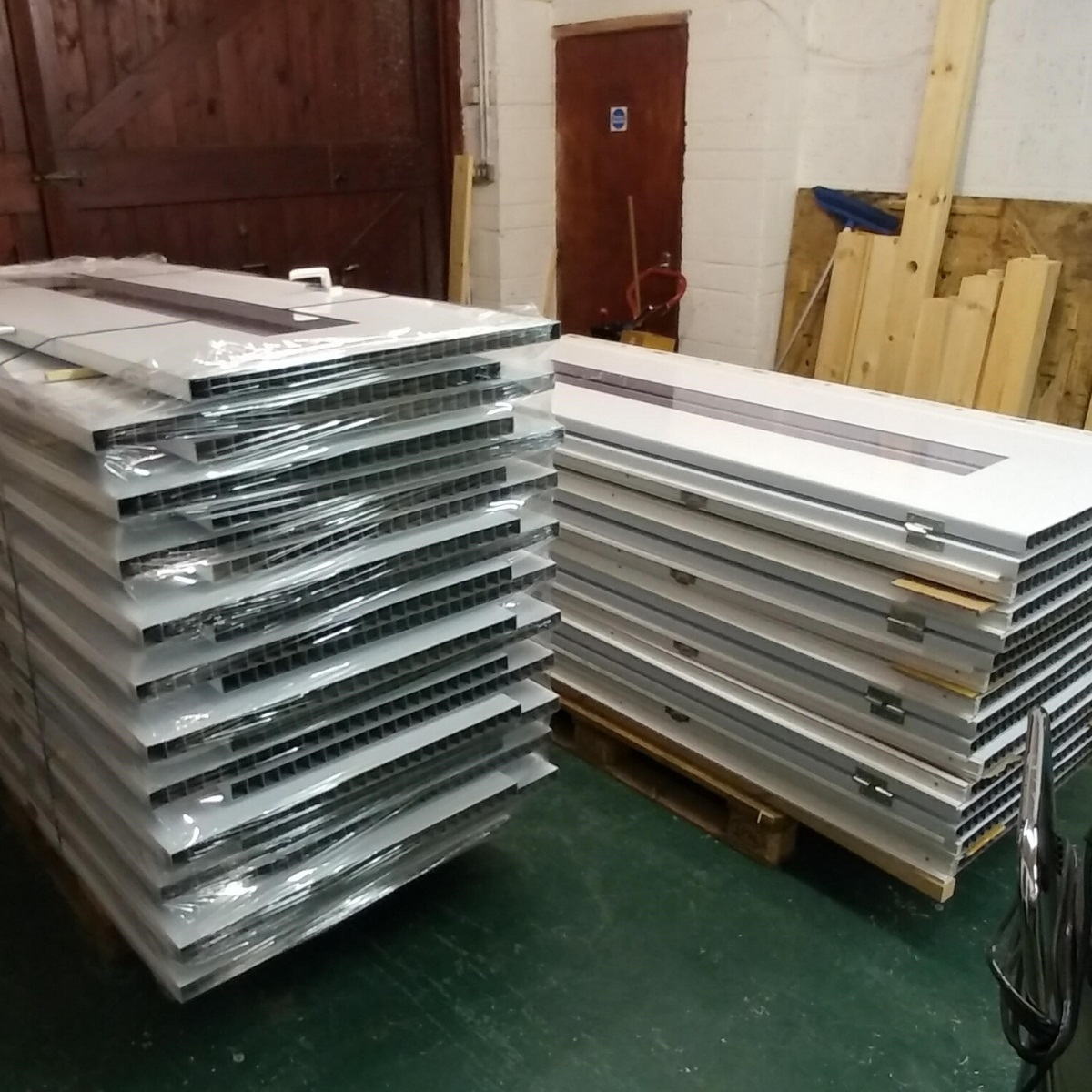 A stack of white plastic hospital doors on a pallet in a workshop ready for dispatch