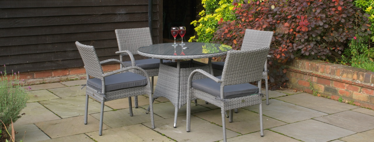 A round rattan outdoor dining table and 4 matching armchairs on a patio