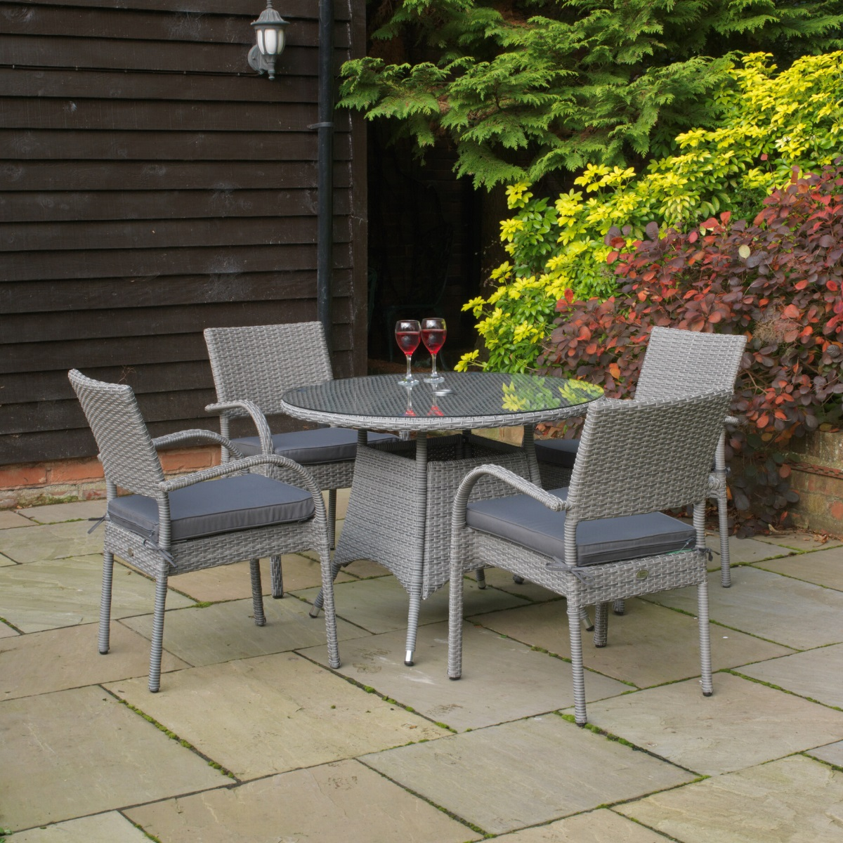 A round grey rattan patio table and matching dining armchairs arranged on a patio