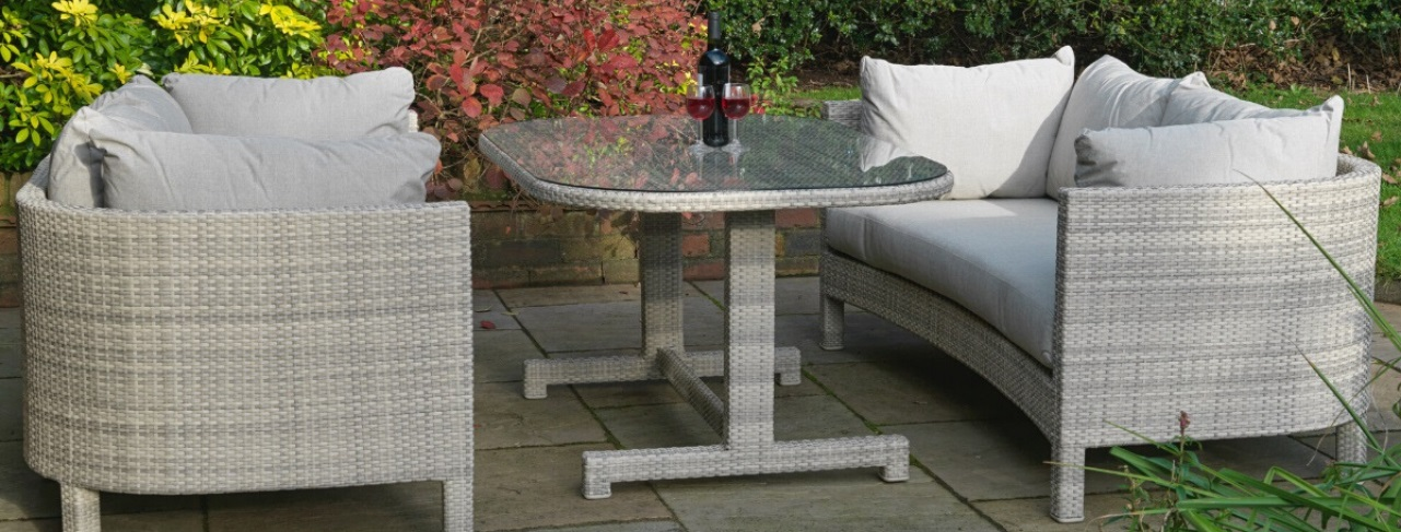 A luxury cream grey rattan outdoor dining table and 2 matching 3 seater sofas with cream cushions on a patio