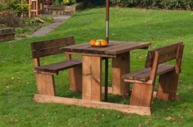 A chunky wooden picnic table for 4 people the bench seats have back rests located on a lawn