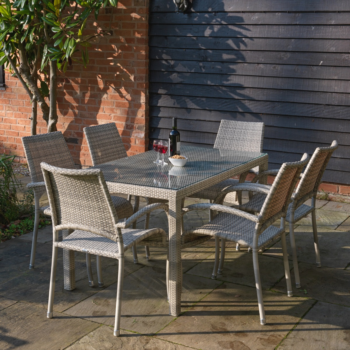 An outdoor rattan rectangular dining table and 6 matching arm chairs on a patio