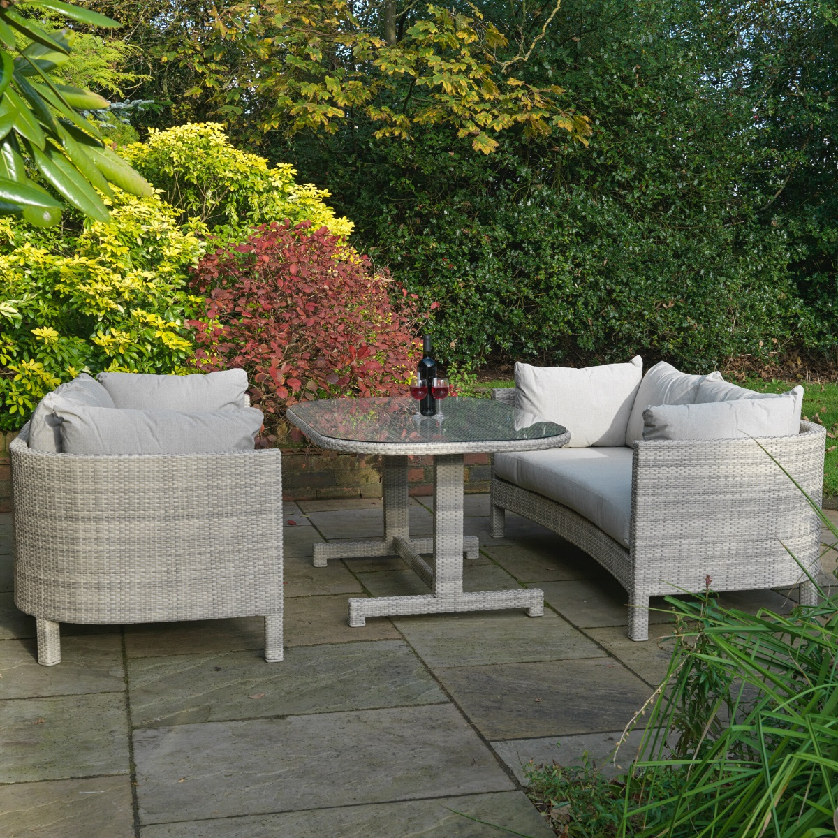 A luxury cream grey rattan outdoor dining table with 2 matching 3 seater sofas on a patio