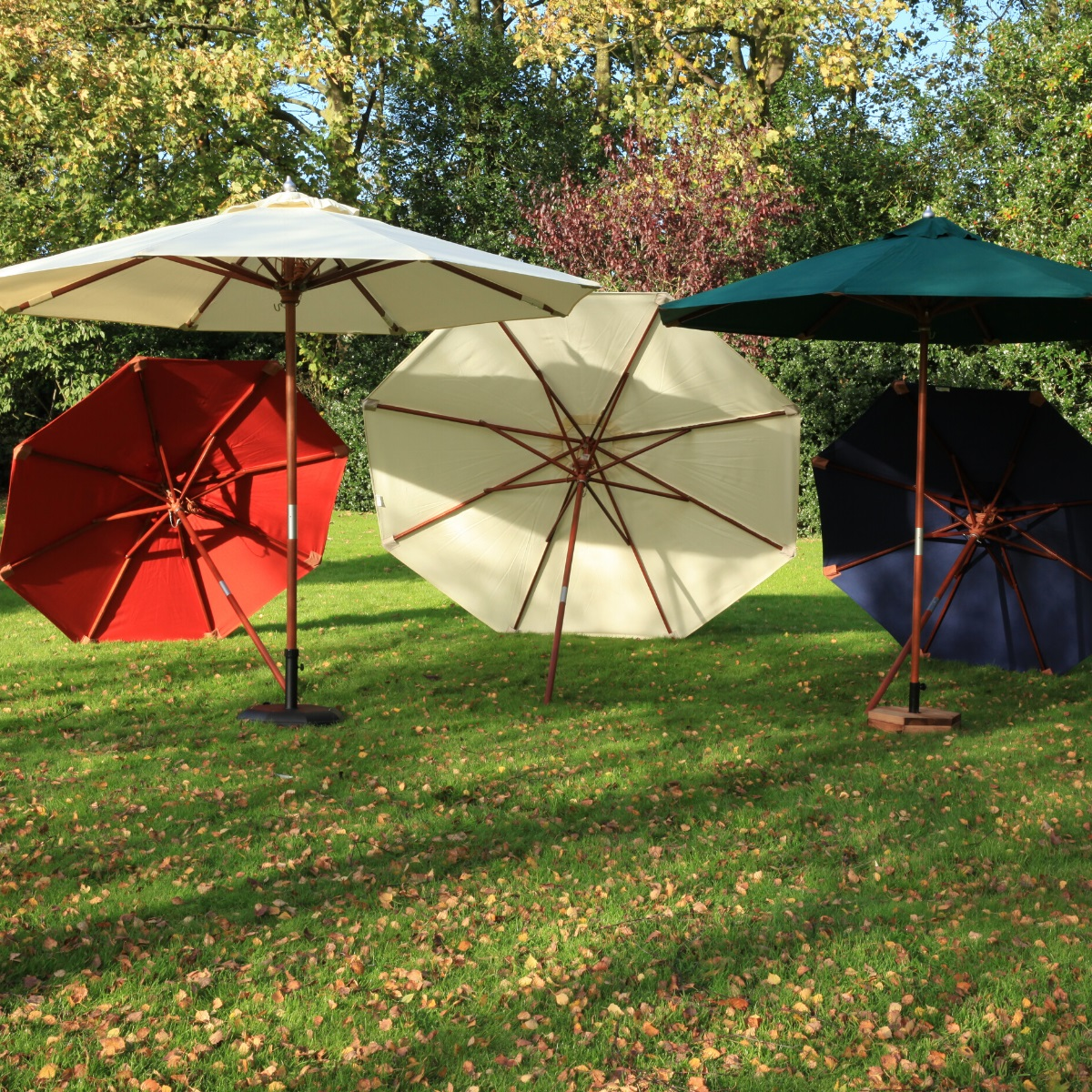 5 parasols in cream, blue, green and terracotta arranged on a lawn