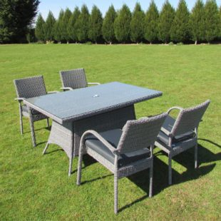 A Rectangular outdoor table and 4 matching chairs in grey rattan with a tempered safety glass table top located on a lawn