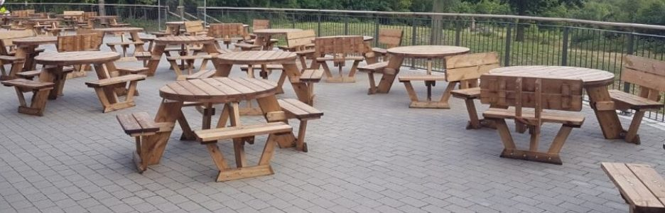 A large patio full of socially distanced 2m apart round wooden picnic tables