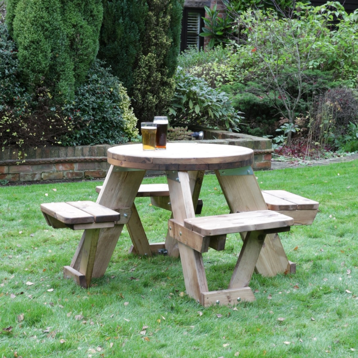 A round 4 seater wooden picnic table located on a lawn