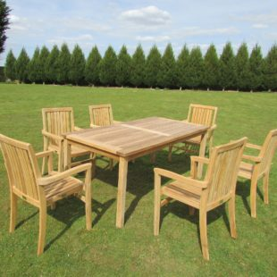 A rectangular teak garden dining table and 6 chairs around it on a lawn