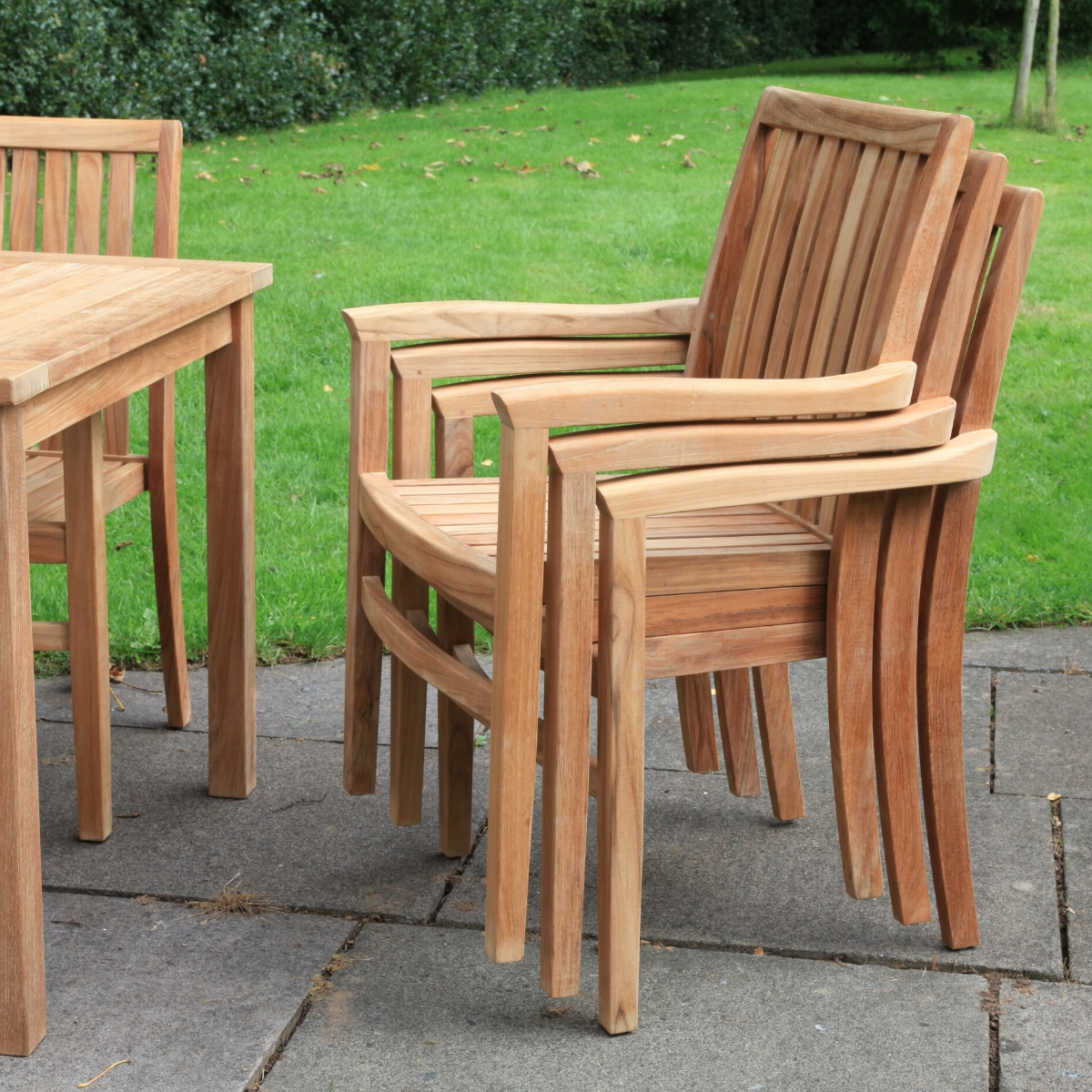 A stack of teak garden chairs on a patio