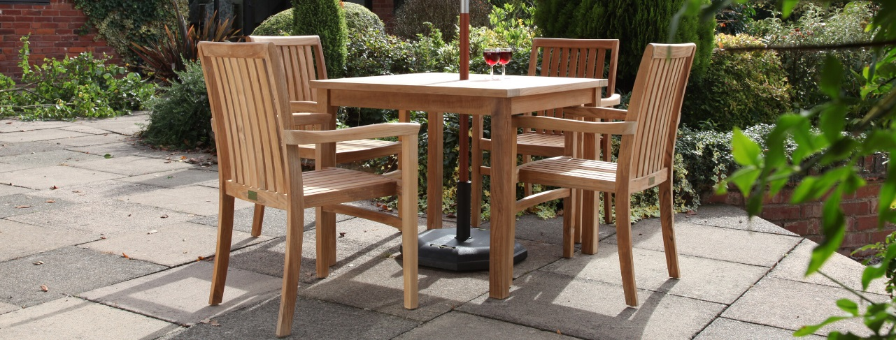 A square teak outdoor table and 4 matching dining armchairs on a patio