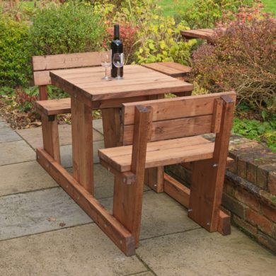 A 2 seater wooden picnic table where the bench seats have backrests loccated on a patio