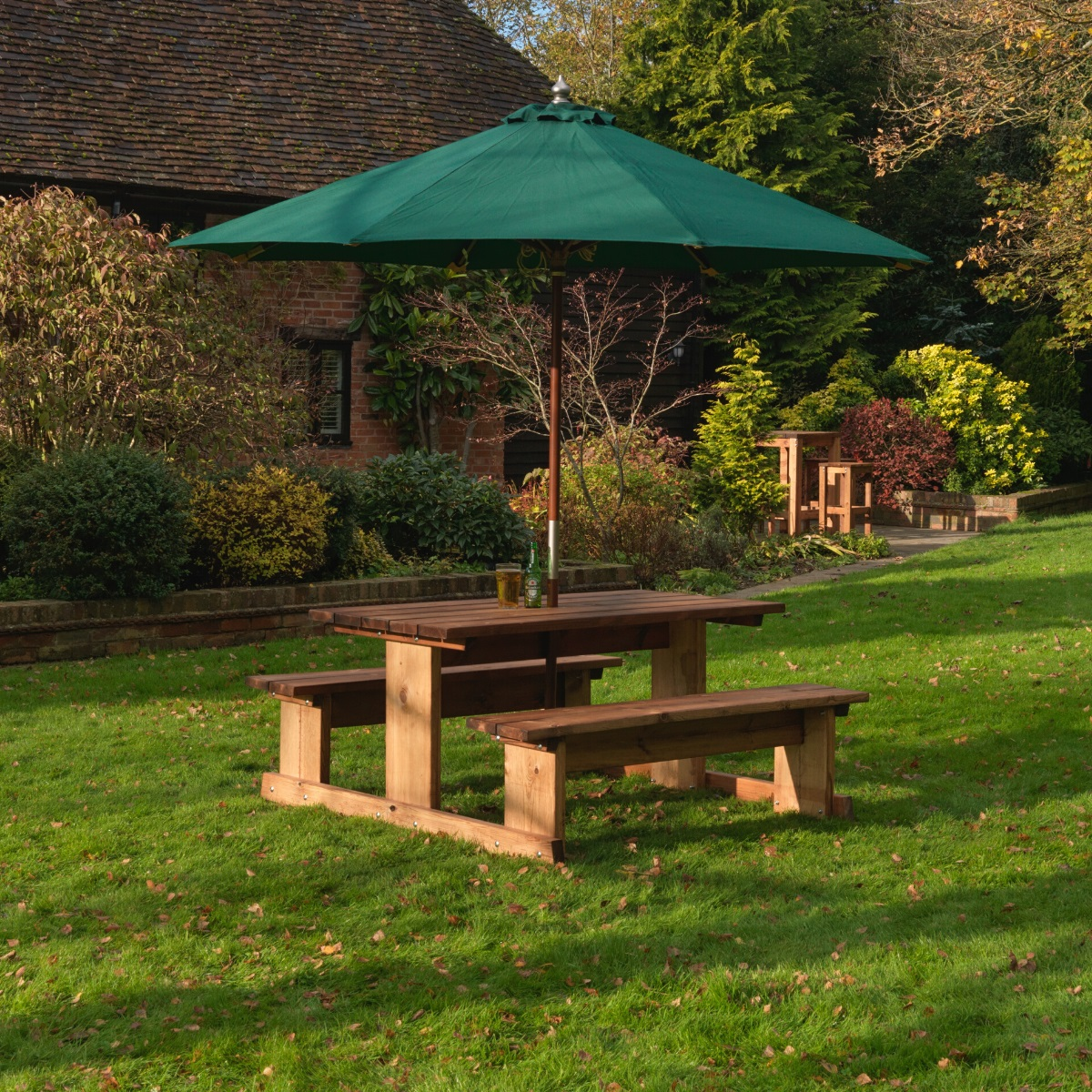 A wooden rectangular picnic table with a green parasol located on a garden lawn