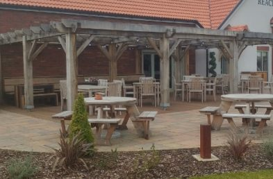 A pub garden patio with spaced out wooden picnic tables for social distancing