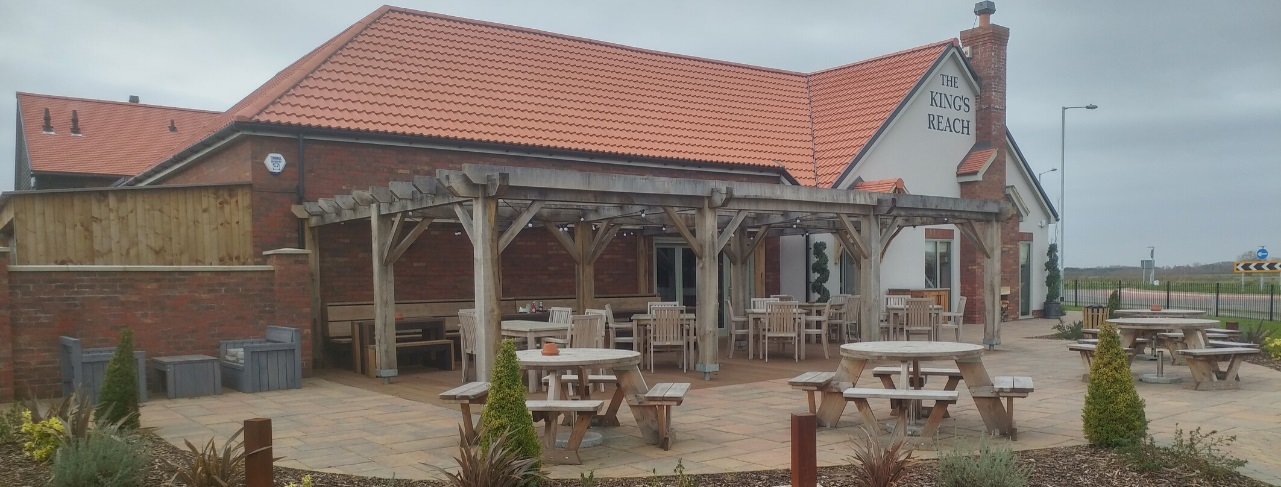 A pub garden with a wooden pergola with circular wooden picnic tables in the foreground and square teak dining tables and chairs in the background