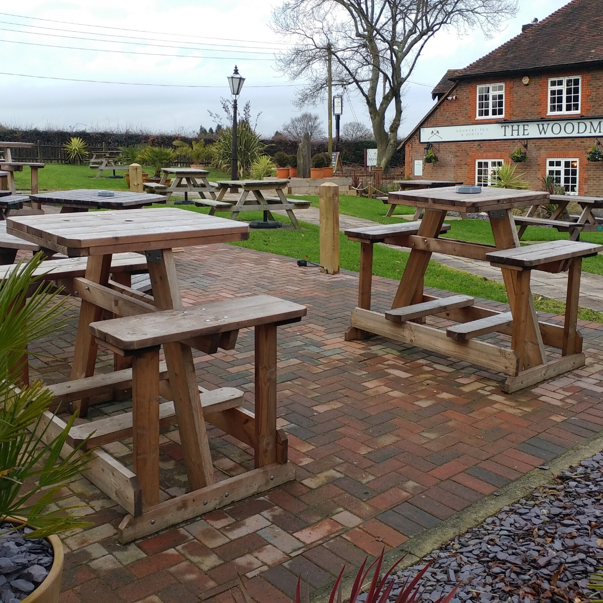A variety of different picnic tables round square and rectangular ones in a pub garden