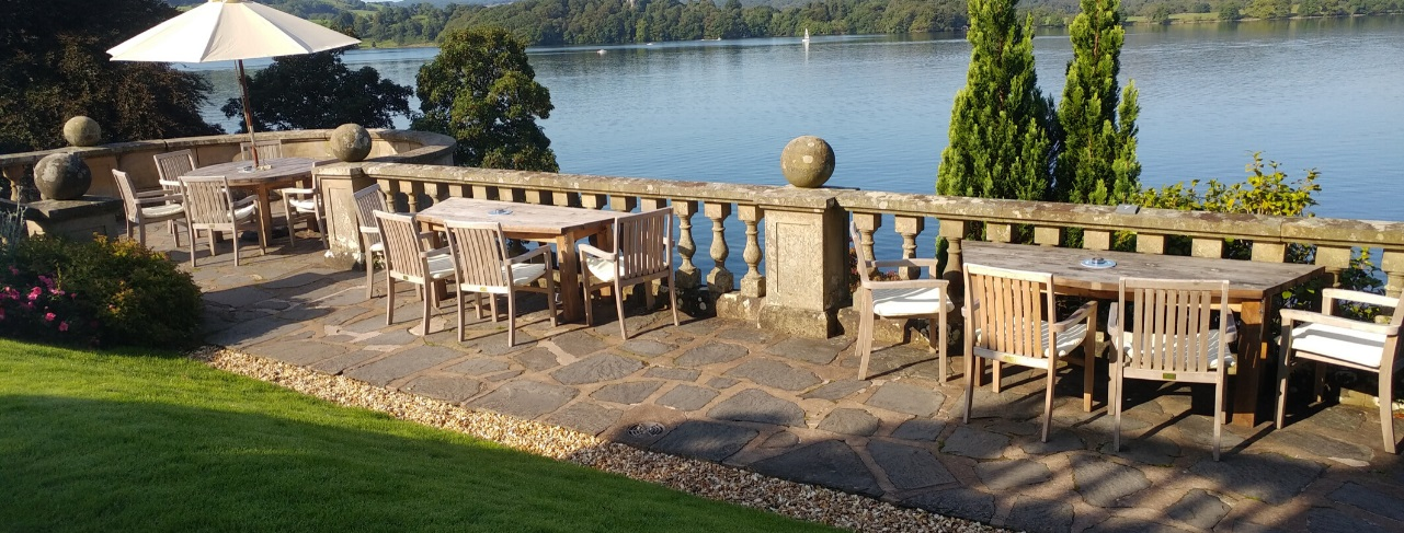 An outdoor hotel terrace over looking the lake with three wooden outdoor dining tables and four chairs around each. One table has a cream parasol