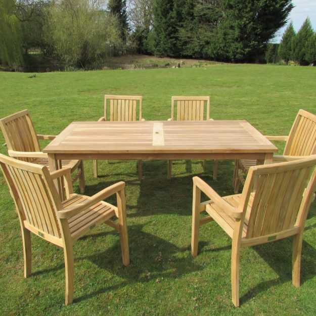 A 1.8m long teak outdoor dining table with 6 chairs around it on a lawn