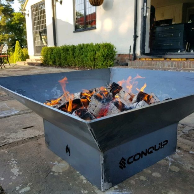 A square metal outdoor fire pit on a patio with burning wood and charcoal inside it