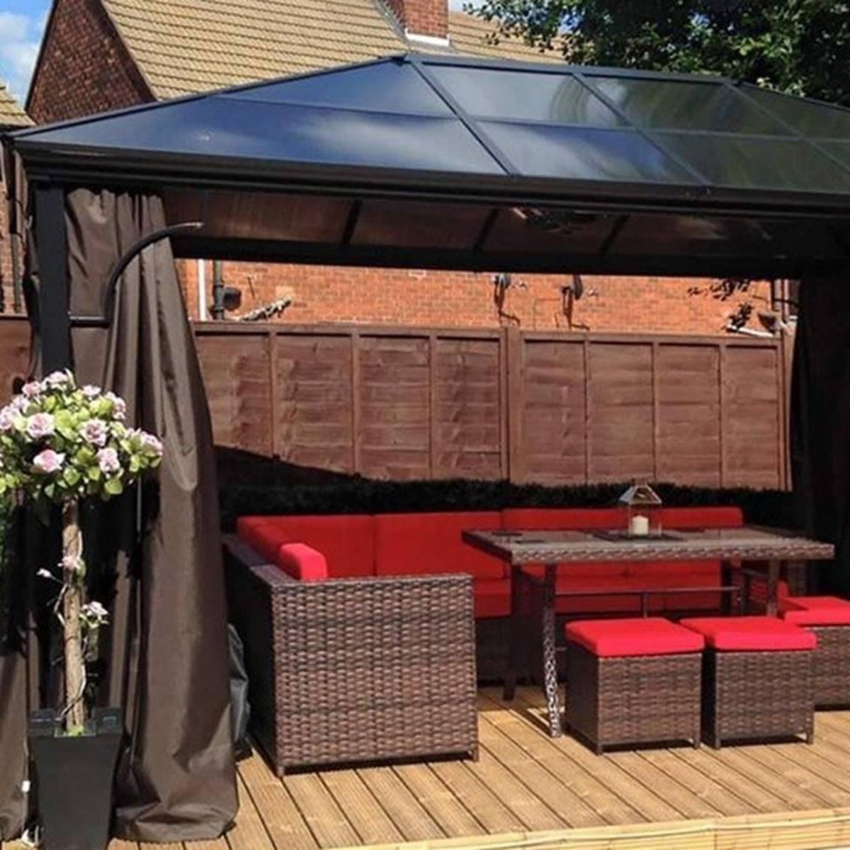 A rectangular metal gazebo with a polycarbonate pitched roof