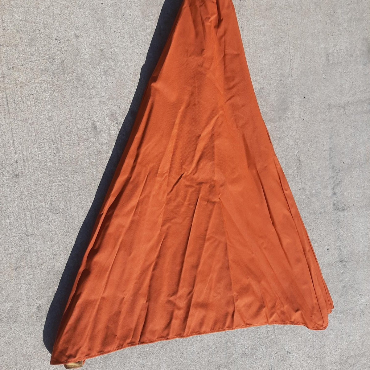 A terracotta canvas canopy for a parasol laid flat on a concrete floor