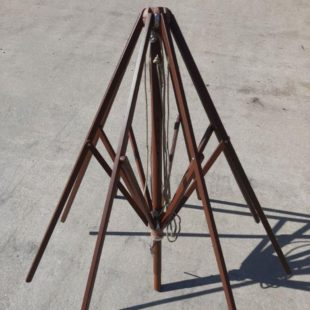 A wooden parasol top spider mechanism as a spare part, shown on a concrete floor partially unfolded