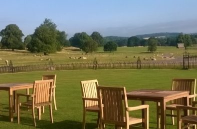Three teak outdoor dining tables with four chairs around each one on a lawn overlooking a field of sheep