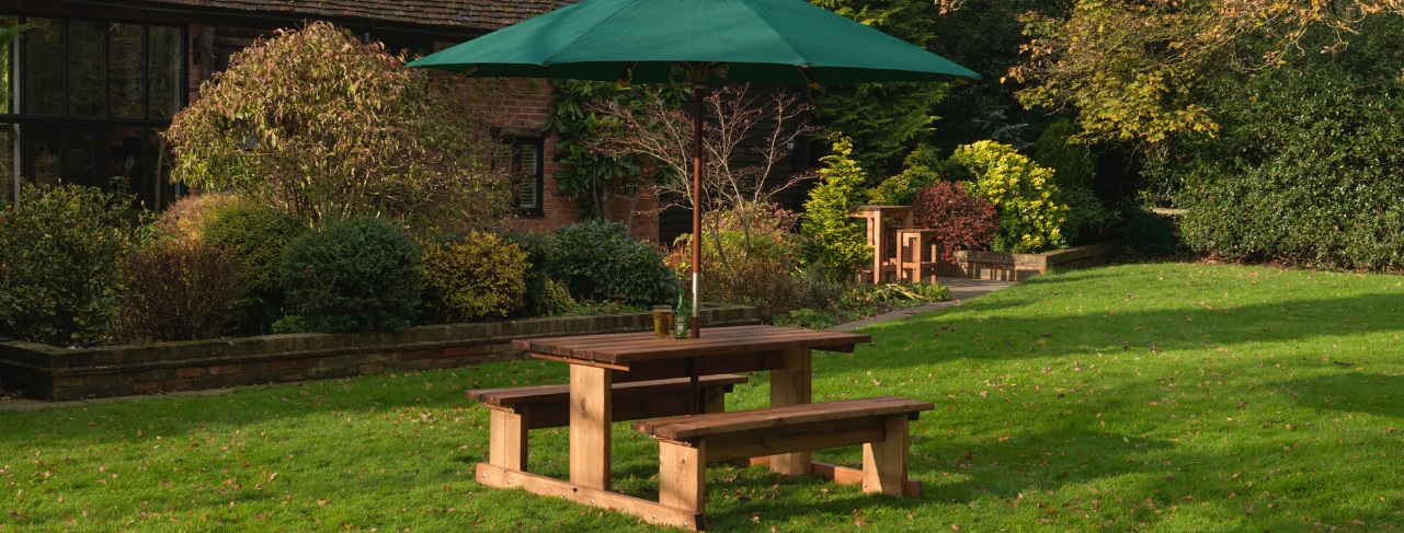 A 4 seater wooden picnic table on a lawn with a green parasol