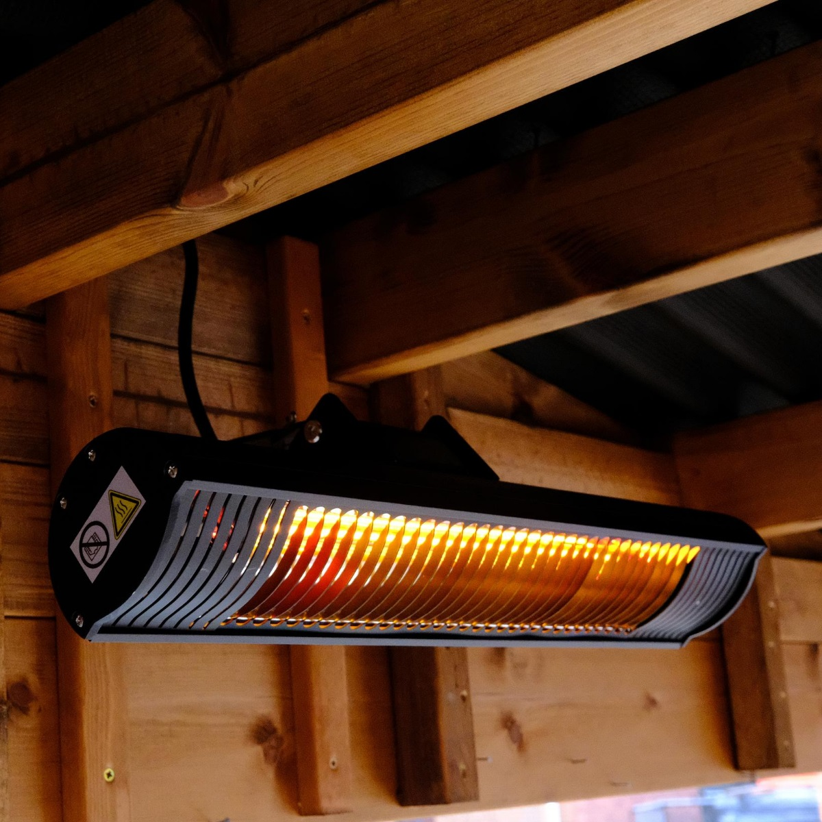 A long rectangular black electric heater mounted on the inside of a wooden outdoor gazebo