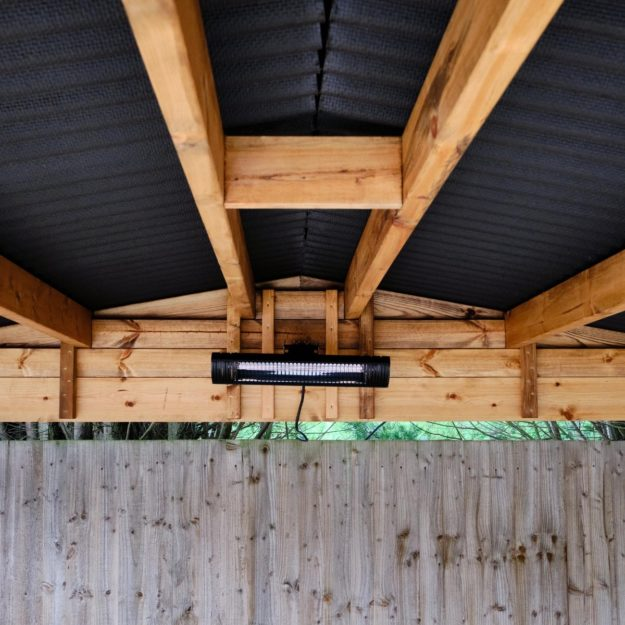 A rectangular electric heater mounted in the roof apex underneath a wooden gazebo