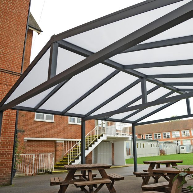 A grey metal framed gazebo with a polycarbonate apex roof on a school playground with picnic tables underneath it