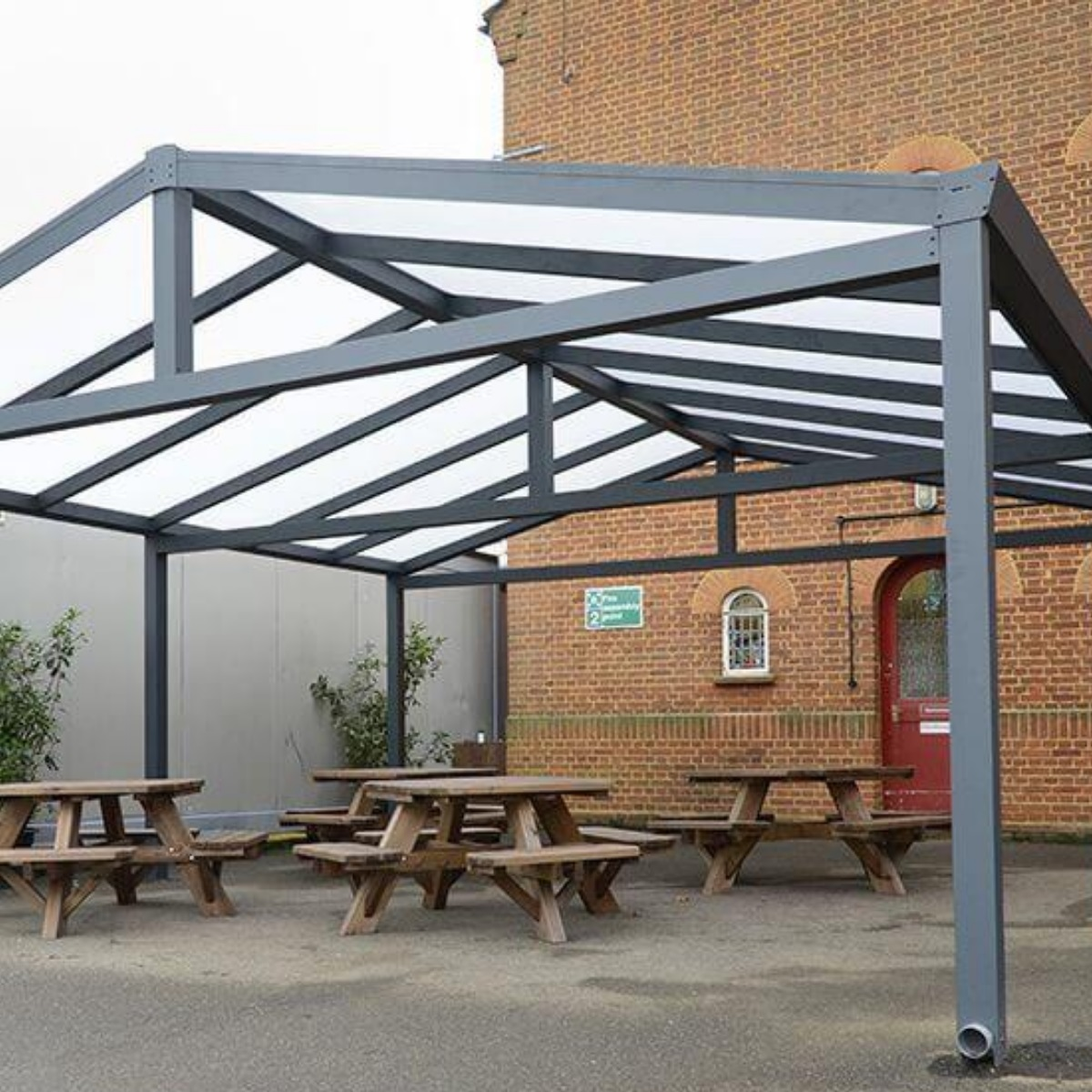 A grey metal framed gazebo with an apex roof made from polycarbonate with picnic tables underneath it