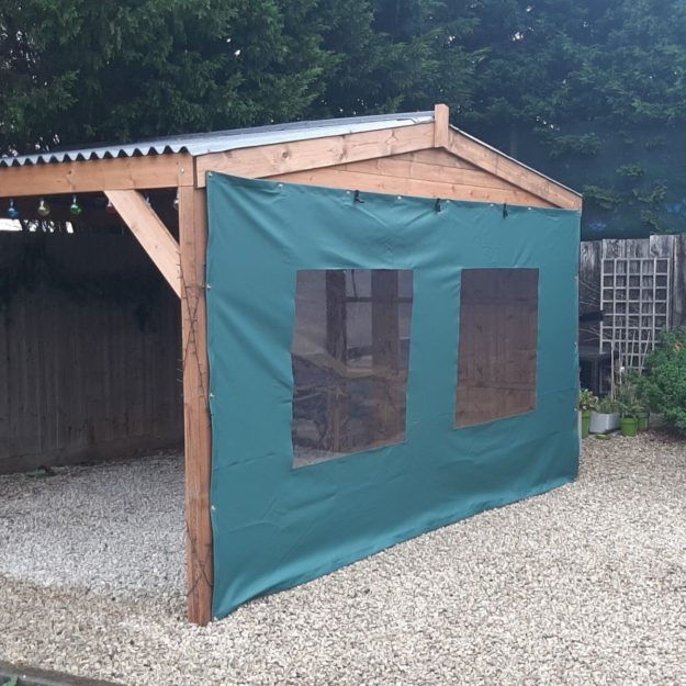 A square wooden gazebo with a pitched roof with a green canvas side panel with clear window panels in on a gravel patio