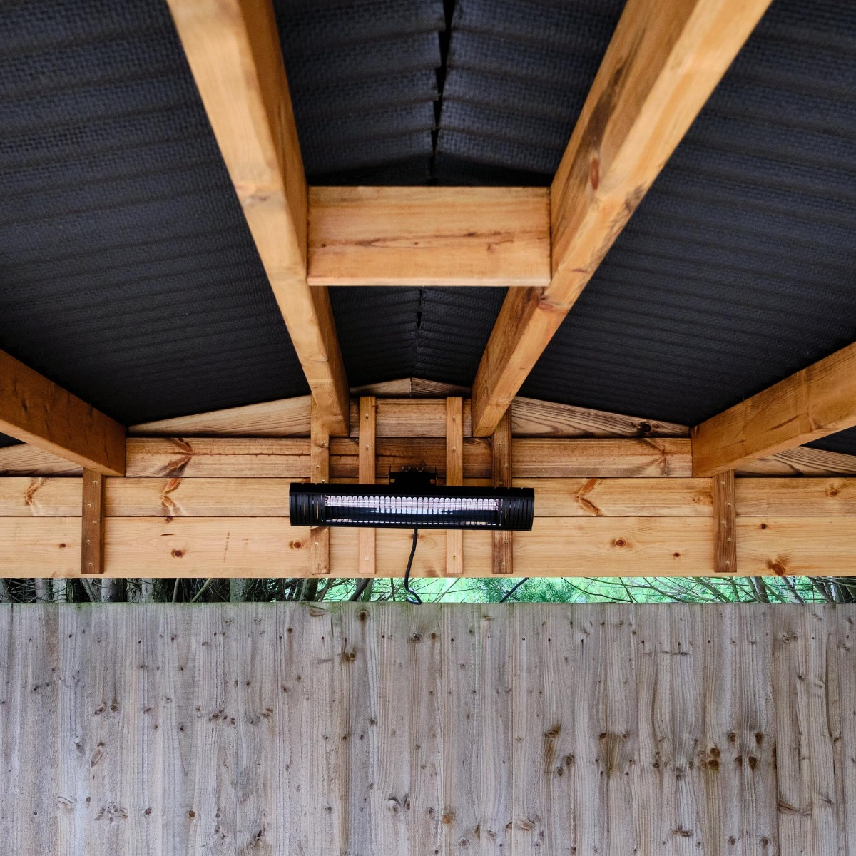 The underside of the apex roof of a wooden gazebo with the beams, composite roof panels and a rectangular electric heater