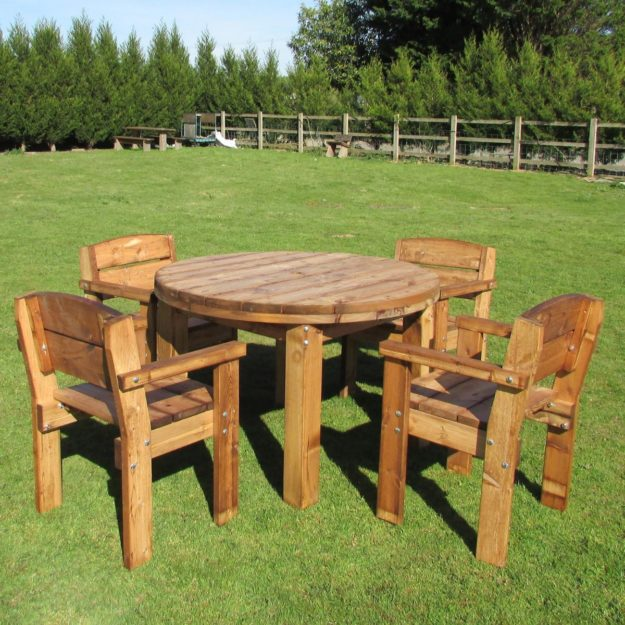 A round wooden table and 4 armchairs located in a field