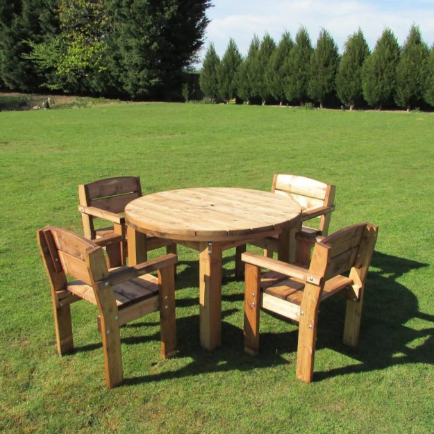 A chunky wooden outdoor round table and 4 arm chairs located on grass