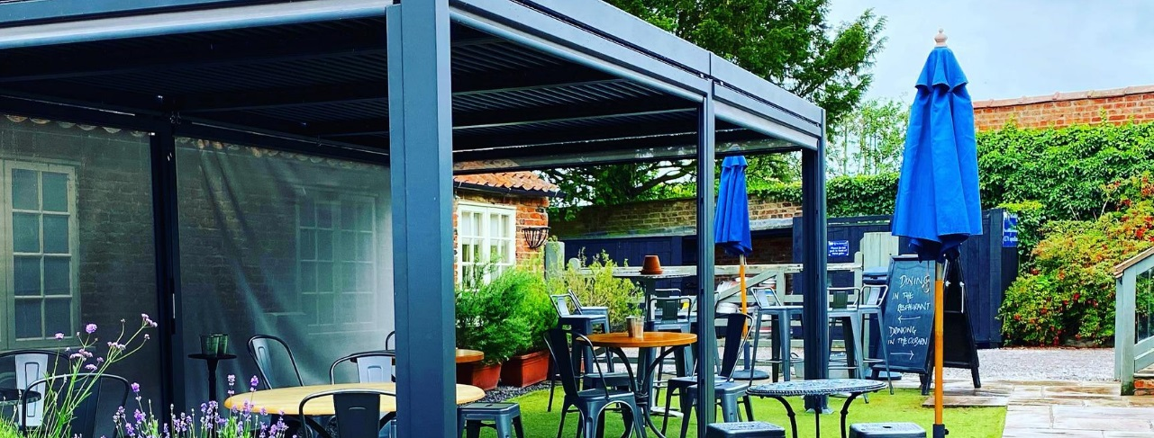 A grey rectangular metal gazebo at a pub with tables beneath it and parasols to the right hand side