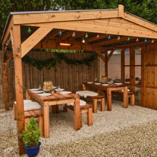A square wooden gazebo with apex waterproof roof with 2 rectangular wooden tables underneath seating 12 dressed for christmas dinner