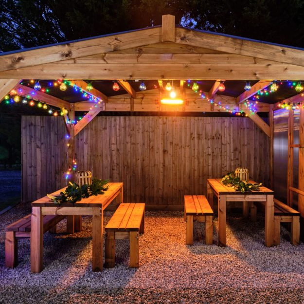 A wooden gazebo with waterproof roof at night time with colourful christmas lights