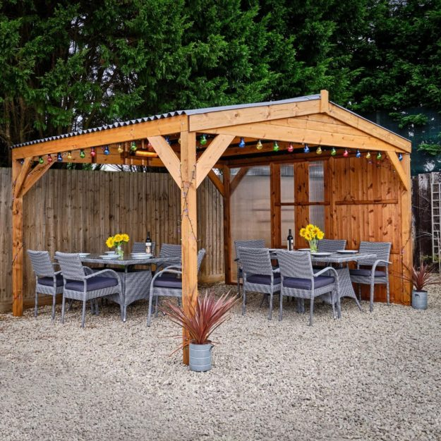 A wooden gazebo with grey rattan outdoor tables and chairs underneath it on a gravel patio