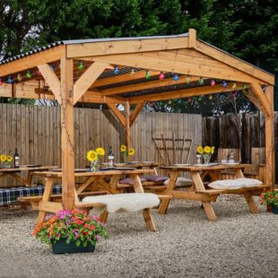 A sqaure wooden gazebo with an apex roof with corrugated composite roof panels with picnic tables underneath