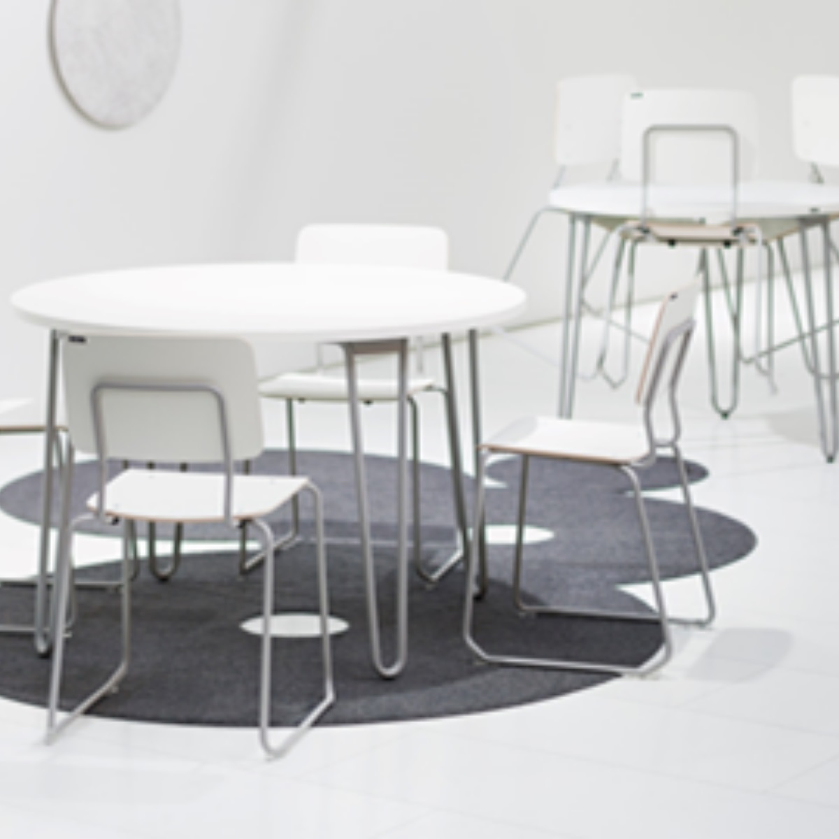 A round table and 4 chairs in a canteen setting. This indoor furniture is anti microbial