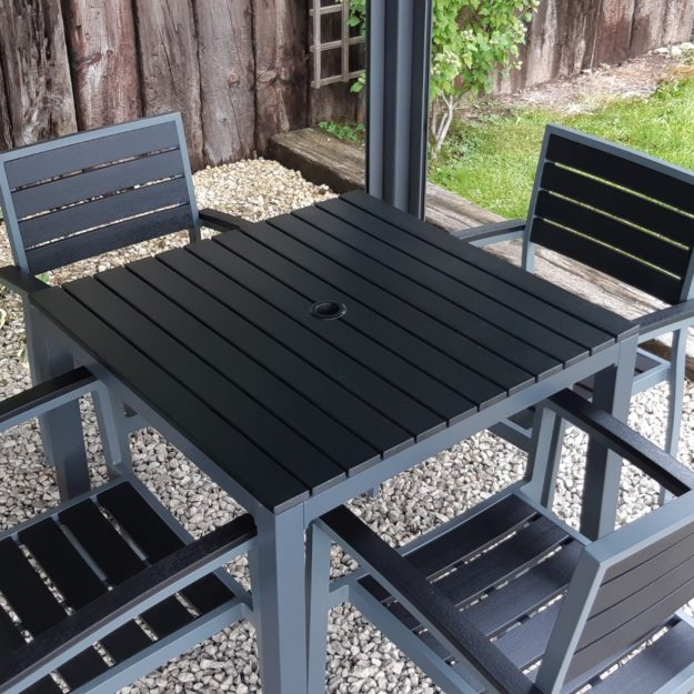A close up of an outdoor table top in black plastic and aluminium with 4 matching chairs around it