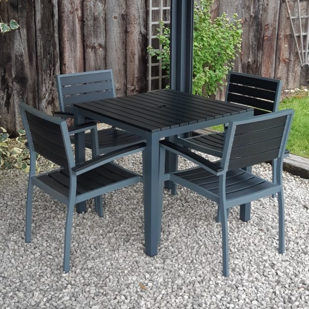 A black plastic and aluminium outdoor square dining table with 4 matching chairs on a gravel patio