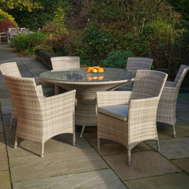 A cream grey weave rattan round dining table and armchairs set on a patio