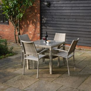 A square cream grey rattan weave outdoor dining table and matching armchairs on a patio
