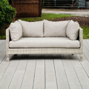 A cream grey weave rattan outdoor 3 seater sofa with cream cushions on a light grey garden deck